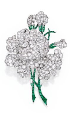 PLATINUM, DIAMOND AND EMERALD BROOCH, CHARLTON & CO. Designed as a peony blossom centered by an old European-cut diamond weighing approximately .90 carat, accented by numerous round, old European and single-cut diamonds weighing approximately 15.00 carats, the stems set with calibré-cut emeralds, signed Charlton; circa 1935.