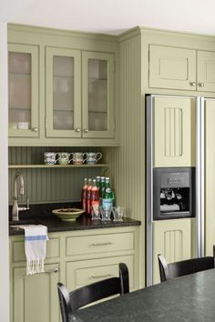 """New cabinets and green-tinged granite with a smudge-proof """"leathered"""" finish blend seamlessly with the existing kitchen. Glass fronts allow light to travel and also reinforce the period look. 