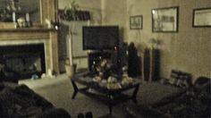 SMALL SHADOW FIGURE BY TV! looks like a black hooded figure to the right of the picture and if you look close over to the left by the couch in corner is of a boy covering his face with his hands…...
