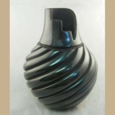 A beautiful and unique hand-coiled, polished vase made by well-known #Jemez artist Emma Yepa. This piece looks similar to a Santa Clara piece, but this black finish is achieved through paint instead of the firing process. Steps are cut in to the rim to represent kachina dancers ascending from the sacred kiva during a ceremony.