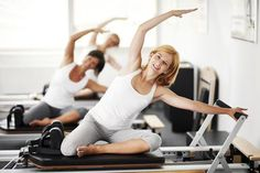 Three women exercising on a Pilates machine. - Kristian Sekulic/E+/Getty Images