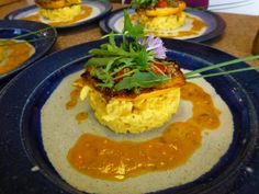 seared garden patty pan squash stuffed with garden veggies & local cheese ON local scrambled eggs, served with a tomato cream, topped with garden arugula
