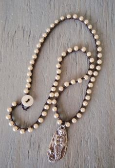 "Mermaid pearl crochet necklace Hidden Heart dainty by slashKnots- Neatly crocheted glass pearls on brown cord. An artisan sterling silver mermaid pendant has an organic look. Reversible pendant has a heart on the opposite side. So easy to wear and looks especially great layered with other silver necklaces!  Necklace measures 17"" -- pendant drop is 1 1/4"". Loop closure with an antique mother of pearl button."