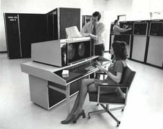 """A CDC 6000. At least judging by the terminal, plus I think I see """"Control Data"""" written on the computer on the left."""