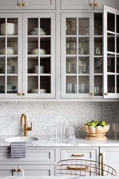 Kitchen Faucets Ideas Steel gray shaker cabinets stacked above glass front cabinets are mounted against small scale marble backsplash tiles over a round sink with a brush gold gooseneck faucet. Classic Kitchen, New Kitchen, Kitchen Decor, Kitchen Ideas, Kitchen Country, Gold Kitchen, Compact Kitchen, Kitchen Black, Kitchen Photos