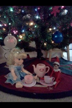 Elf having a tea party with dollies/teddies.