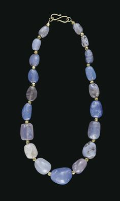 A WESTERN ASIATIC BLUE CHALCEDONY BEAD NECKLACE  CIRCA 2ND CENTURY B.C.-2ND CENTURY A.D.  Composed of irregular beads, graduated in size, interspersed with modern gold beads; strung with a modern S-hook closure