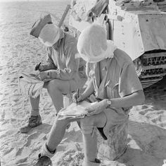 Two members of a Crusader tank's crew write home before setting off on patrol in the Western Desert, 28 August 1942. Note the mosquito nets round their faces to keep the flies away.