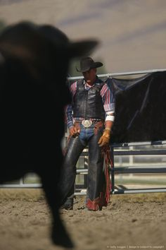 Rodeo, cowboy standing beside fence, looking at bull #cowboy #fashion At Eagle Ages we loves cowboy boots. You can find a great choice of second hands & vintage cowboy boots in our store. https://eagleages.com/shoes/boots/men-boots/cowboy-boots.html
