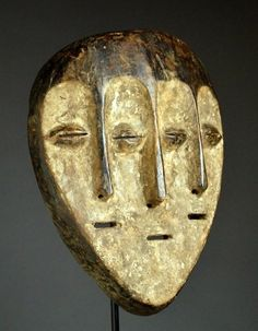 Africa | Triple face mask from the Lega or Lengola people of DR Congo | Wood, white kaolin, encursted patina | ca. early to mid 20th century
