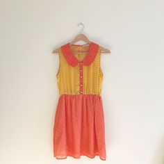 """Peter Pan Collar Coral & Yellow Babydoll Dress Darling coral & yellow Peter Pan collar dress from ModCloth.  Elasticated waist. Decorative yellow buttons down the front.  Button closure at neckline and back. Bodice is shear and the skirt part is lined.  Medium.  Could fit a large. By Fun 2 Fun.  Lightweight polyester.  19"""" across bust/13-17"""" waist/33"""" length.  Great condition. Back neck button was replaced with a slightly larger mint green button because the original button kept coming…"""