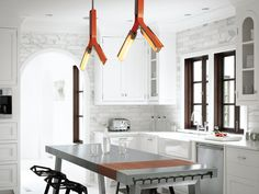 Modern kitchen with Rich Brilliant Willing overhead lighting, tainless steel kitchen island by Bulthaup, plastic stacking stools designed by Konstantin Grcic for Magis.