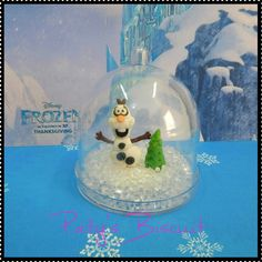 """Cúpula decorada estilo """"globo de neve"""" Olaf, com gelo falso em acrílico. <br> <br>Produto sob encomenda. Valor unitário. <br>Material: biscuit; cúpula acrílica (7x7cm). Altura da miniatura: 3cm. <br> <br>Antes de encomendar, não esqueça de conferir as políticas da loja (http://www.elo7.com.br/patysbiscuit/politicas ), e de entrar em contato para consultar disponibilidade na agenda!"""