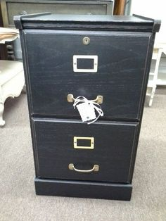 $69 - This wooden file cabinet has two smooth pulling drawers with brass hardware, it has been painted black lightly distressed and finished with wax. It measures 16 inches across the front, 16 1/2  inches  deep and stands 27 inches tall. The file cabinet can be seen in booth A6 at Main Street Antique Mall 7260 East Main St ( E of Power Rd ) Mesa 85207  480 9241122open 7 days 10 till 530 Cash or charge accepted