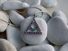 Colgante tradicional simbolico de plata, esmeraldas y rubis.
