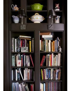 Bookshelves hold a fraction of Marie Nygren's cookbook collection. Above are her most colorful serving pieces.   - HouseBeautiful.com