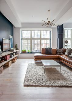 love the navy blue wall, light, couch Audrey's Cozy Industrial Soho Apartment