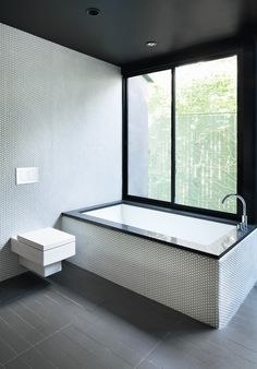 """For the bathroom inside a renovated Hollywood bungalow, architect Noah Walker used a simple palette of gray and white tile, black countertops, and stainless steel fixtures. """"I love minimal bathrooms with natural light, so less is more, and pay attention to the details,"""" he advises."""