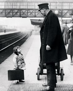 A young passenger asks a station attendant for directions. Bristol Railway Station, England, 1936, by George W. Hales.