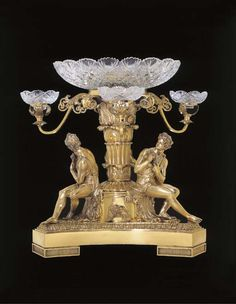 MARK OF PAUL STORR, LONDON, 1809<br>The triform base with acanthus border, supporting a central acanthus decorated column surrounded by three seated classical figures wearing the pelt of the Nemean lion, each playing a pipe, with applied bacchic masks between, supporting a central cut-glass bowl and three smaller cut-glass bowls each on a foliate scroll arm, altered, interior with iron support, <I>marked under base, on standard, each pelt</I>, the base stamped RUNDELL BRIDGE ET RUNDELL ...