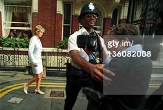Princess Diana, on the day her divorce from the Prince of Wales was announced, with a policeman holding back a photographer, St. James', London, 12th July 1996. (Photo by Martin Godwin/Getty Images)