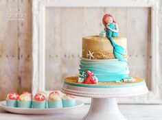 The ever-charismatic Sebastian, surprises Arielwith a pile of  prettily-wrapped gifts in thisLittle Mermaid-inspired birthday cake.  Classic white cake with vanilla buttercream, and of course, a matching set  of vanilla swirl cupcakes, each with a beach themed topperto go along with  it. I'm