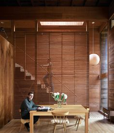 Dolce sits at the dining-room table in front of the elegantly slatted cypress divider, which separates the living space from the new staircase.  Photo by Raimund Koch.