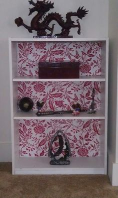 Renewed bookcase craft - modge podged fabric on back panel; nice way to add texture to plain white military housing walls.