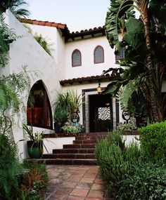 Spanish-style home with lush tropical-inspired garden and terracotta tiled walkway and stairs.