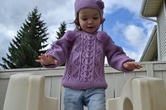 "This heirloom quality sweater uses twisted cables, bobbles and chain stitches. The hat has three pompoms, one on top and two on sides, has attached neck warmer on the back and a heart of chain stitches on the side. This is for 2- to 4-years olds; however, it can be easily transformed for young girls. Finished chest size is 23"" ~ 25""."