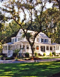 Big white house with lots of windows, trees, and a wrap-around porch...