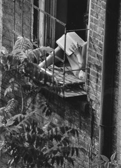 André Kertész, Greenwich Village, New York (woman reading in fire escape window) 1963