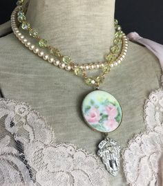 I hung a petite vintage Art Deco rhinestone dress clip vintage hand painted porcelain rose brooch, and draped these both from vintage pale yellow aurora borealis crystals. I also added a chain of vintage glass pearls and secured everything at the back with a vintage rhinestone and faux pearl clasp. Approximately 16 inches with 3-inch pendant drop and absolutely one of a kind.  Please also visit me at:  Jewelry supplies - www.thepariscarousel.etsy.com Newsletter - http://eepurl.com&#...
