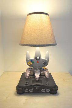 Nintendo N64 Desk Lamp - Console and Controllers - N64 Light Sculpture With Lamp Shade  This is a very unique lamp sculpture I made using an authentic Nintendo 64 console and 2 controllers. The system and the controllers no longer worked so I recycled them into something new and functional. The two controllers can be turned and positioned in many ways giving this piece a fun interactive quality. All the buttons on both controllers can be pressed like normal and the analog stick on the bottom…