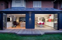 Architectural design extension with open windows, decking, lounge and modern white kitchen. Interior, exterior, dusk, no people and pink chairs | andy spain photography