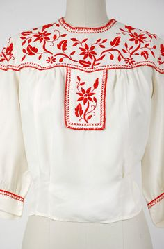 Vintage 1940s acetate peasant blouse, an ivory color with cherry red embroidery. The silhouette is classic, darted to the waist, but blousey and gathered into the yoke. The yoke is elegantly embroidered with a vine like floral and classic edging. The half-length puffed sleeves are cuffed.