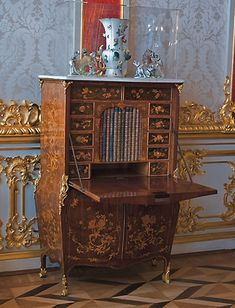 The Crimson Pilaster room of the Catherine Palace contains a secretaire made by the German master craftsman Abraham Roentgen (1711–1793) – a rare example of inlaid furniture in the feathery Rococo style typical of the products of his celebrated workshop from 1765 into the 1770s.