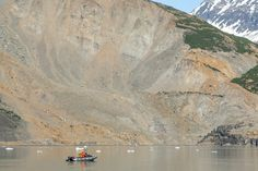 The giant scar of the landslide is put into perspective by the skiff surveying the damage. PHOTO BY BJØRN OLSON, COURTESY OF GROUND TRUTH TREKKING