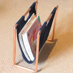 Create a modern magazine rack with copper pipes, fabric and glue.