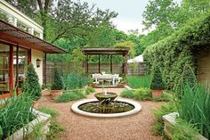 A slatted arbor shades a sitting area at one of this courtyard. Pots of seasonal flowers by the table and chairs add a spot of color to a palette of mostly greens, browns, and grays. A lattice fence helps screen the neighbor's house from view.      See more of this Heat-Tolerant Austin Garden