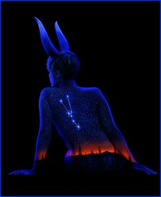 """Bodyscapes"" is a body art series by artist John Poppleton ""Under Black Light"" that uses fluorescent pigment to paint landscapes on female models. He then photographs the models under UV light for the final fluorescent effect."
