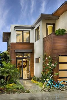 Modern house with stucco and horizontal wood slat exterior. Concrete work with grass coming through. Great modern silver house numbers.