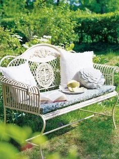 Adorable wrought iron white bench with scrolls and cute cushion in the garden