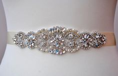Flower Girl, Girl, Wedding Belt, Bridal Belt, Bridesmaid Belt, Bridesmaid Belt, Crystal Rhinestone Sash Ready to ship This beautiful sash is made with double faced satin ribbon and a rhinestones crystals trim is attached to it. Edges of the sash heat sealed, so they do not risk fraying. It will look great with any color dress, being either white, diamond, ivory, or antique. Looks lovely in the front , or on the side !  Such a nice gift for the lovely girl ! Can be worn also as a headband…