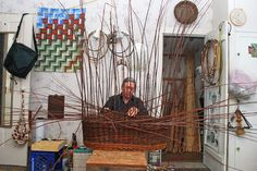 Katherine Lewis weaving a willow bassinet in her workshop.