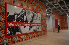 A jaw-dropping hang of work from the 1980s: Barbara Kruger, Untitled (We Don't Need Another Hero) (1987) in front with Donald Moffett's He Kills Me (1987) wallpaper.