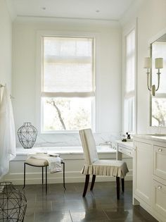 Transitional bathroom features an ivory wainscoted tub with a marble deck and backsplash placed under windows dressed in a natural linen roller shades.