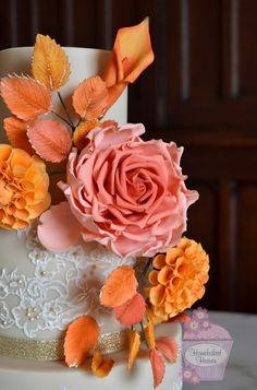 Autumnal wedding cake with giant sugar rose, dahlias and calla lily, and leaf…