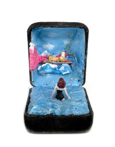 """In Toronto-based artist Talwst's dioramas, antique ring boxes become tiny theaters where spectacularly detailed scenes unfold on a miniature scale. The artist began his unique hobby when a vendor at a Paris market handed him an old ring box and said, """"I want to see you do something with this."""" Talwst turned it into a seaside scene featuring a woman in a black, vintage swimsuit, and his spectacular series was born. """"I want the viewer to open the box and feel they have been transported to…"""