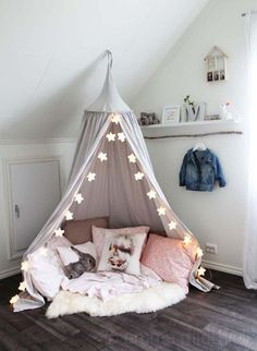 What little girl wouldn't love this reading nook and quiet hangout in their room. The #FairyLights are such a cute accessories. #ReadingNook #GirlsRoom